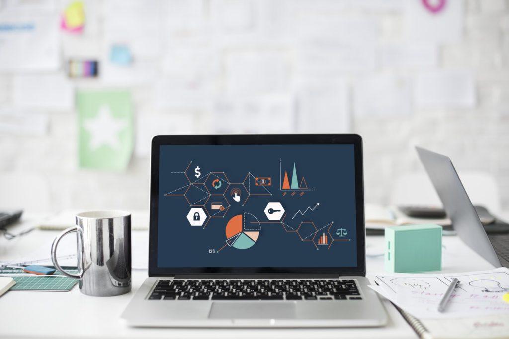Laptop sitting on an office desk with infographics regarding digital marketing