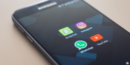 Phone laying on a table unlocked with social media icons such as snapchat, instagram, whatsapp and youtube.